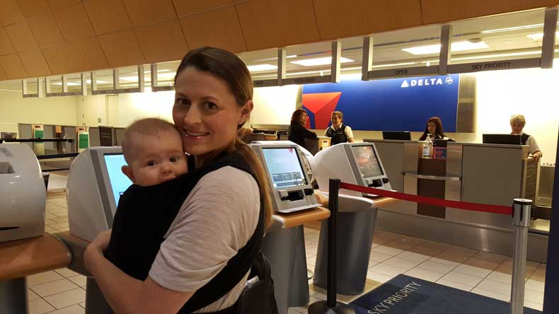 Baby carriers for travel 2019 - mom wearing baby wrap at airport
