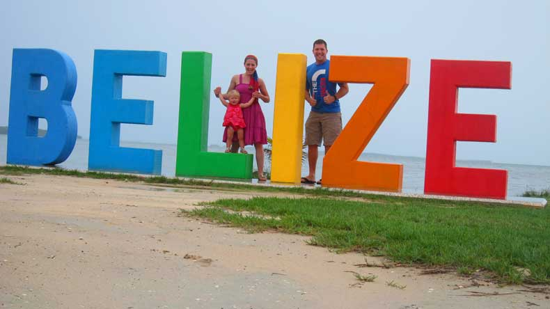 family on vacation in Belize in front of the Belize sign