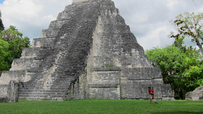 Tikal National Park with a toddler and father walking in front of a pyramid