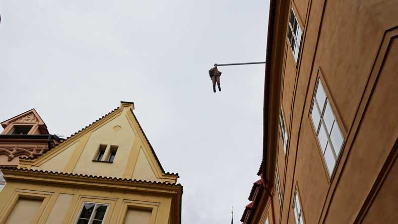 Statues in Prague - man hanging from building