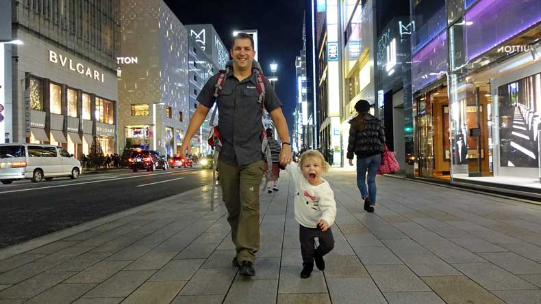 Family travel in Japan father and daughter walking down street.