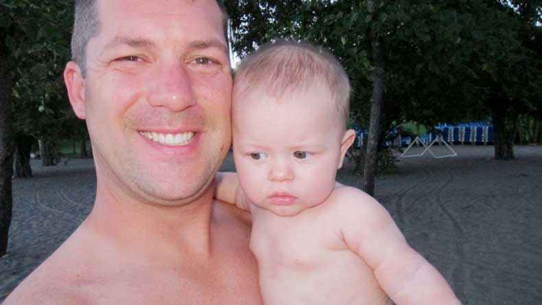 Father and baby on beach in Costa Rica at 4:30 in the morning