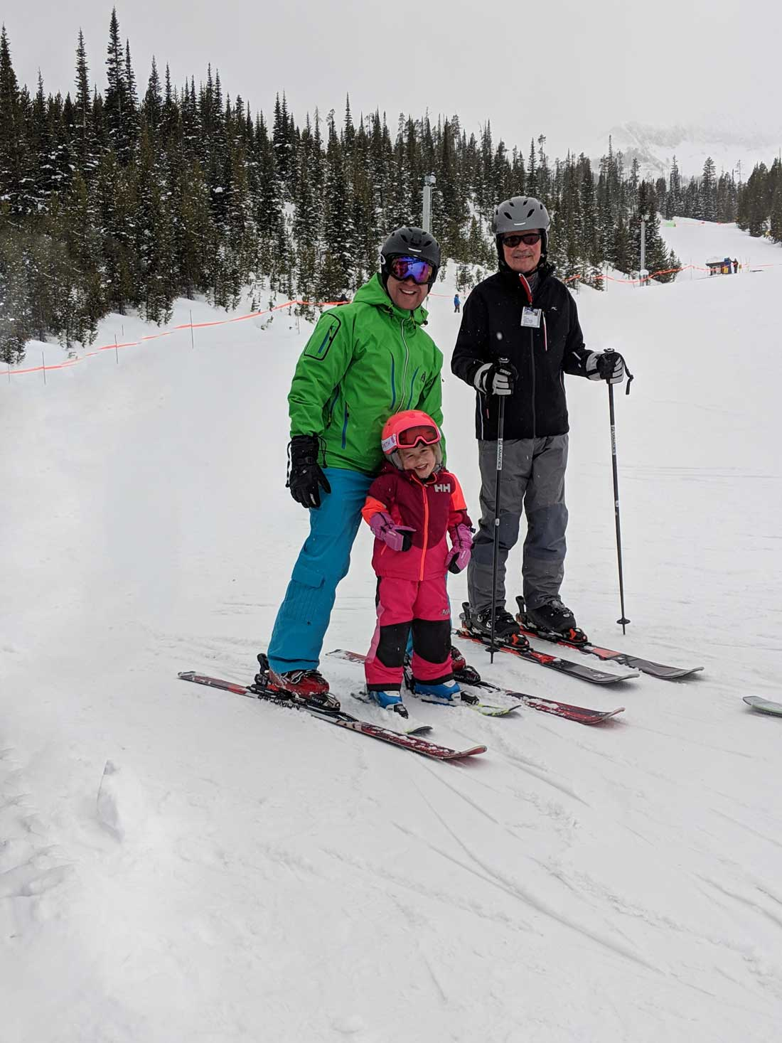 3 year old skiing with dad and grandpa