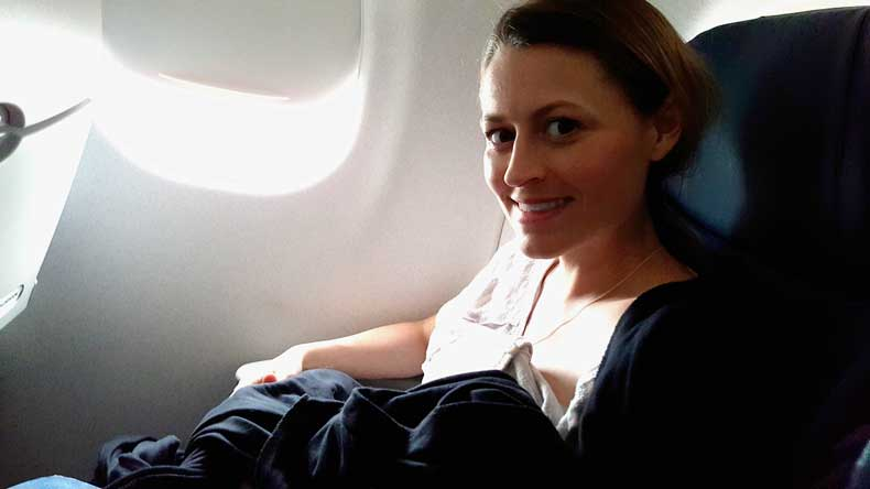 babywearing for travel - mom on plane with a baby