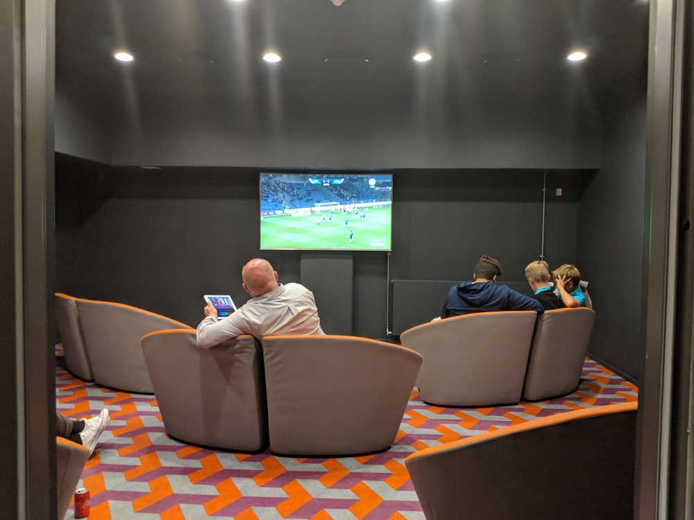 The TV room at a hostel with kids and a parent