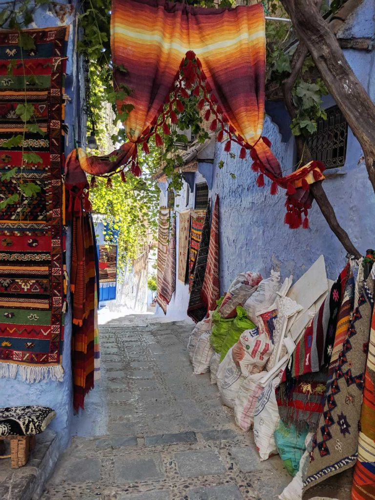 Small street in the medina lined with Moroccan rugs and tapestries.