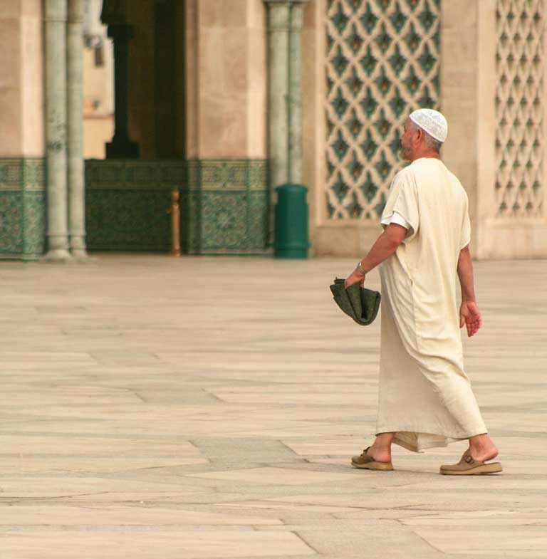 Muslim man walking into a mosque in Morocco, where one of the most interesting facts about Morocco is that 99 percent of the population is Muslim
