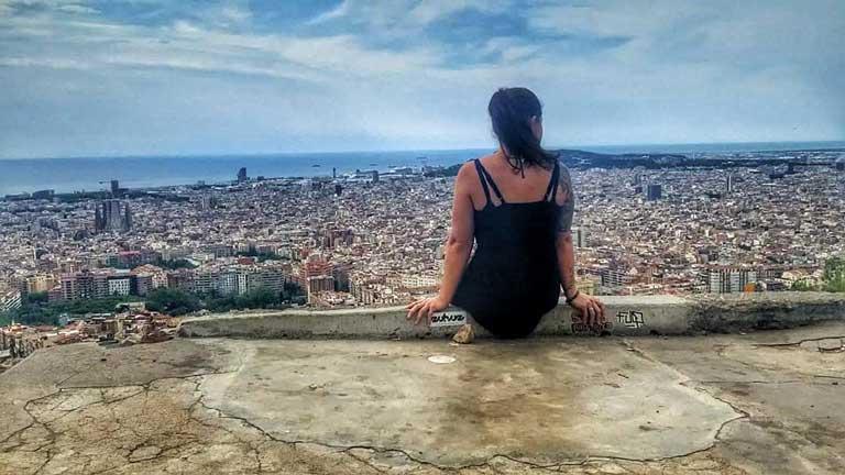 woman sitting on los bunkers overlooking Barcelona Spain