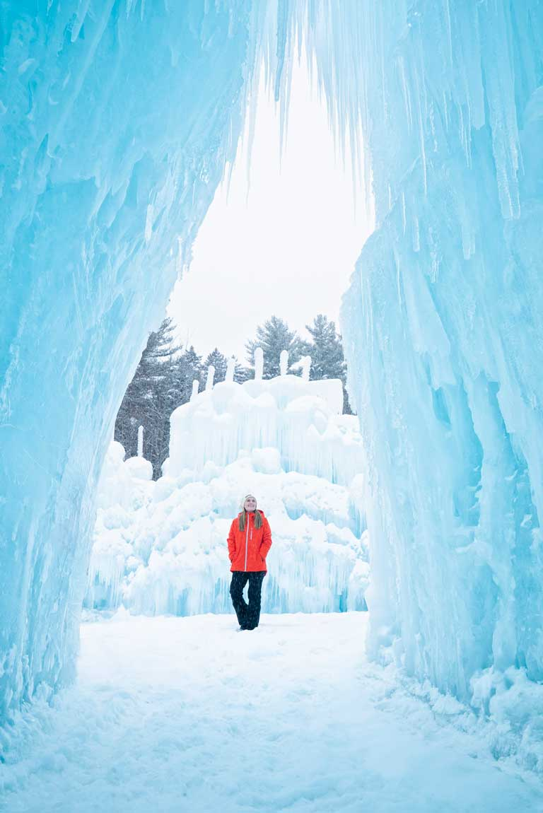 Standing underneath an archway on a snowy day at Ice Castles