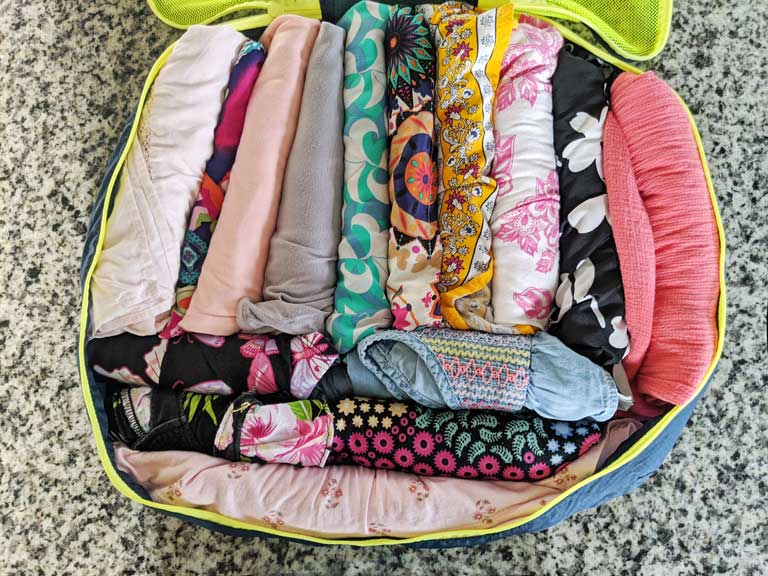 Packing for a baby - baby clothes for travel rolled and packed into a single packing cube