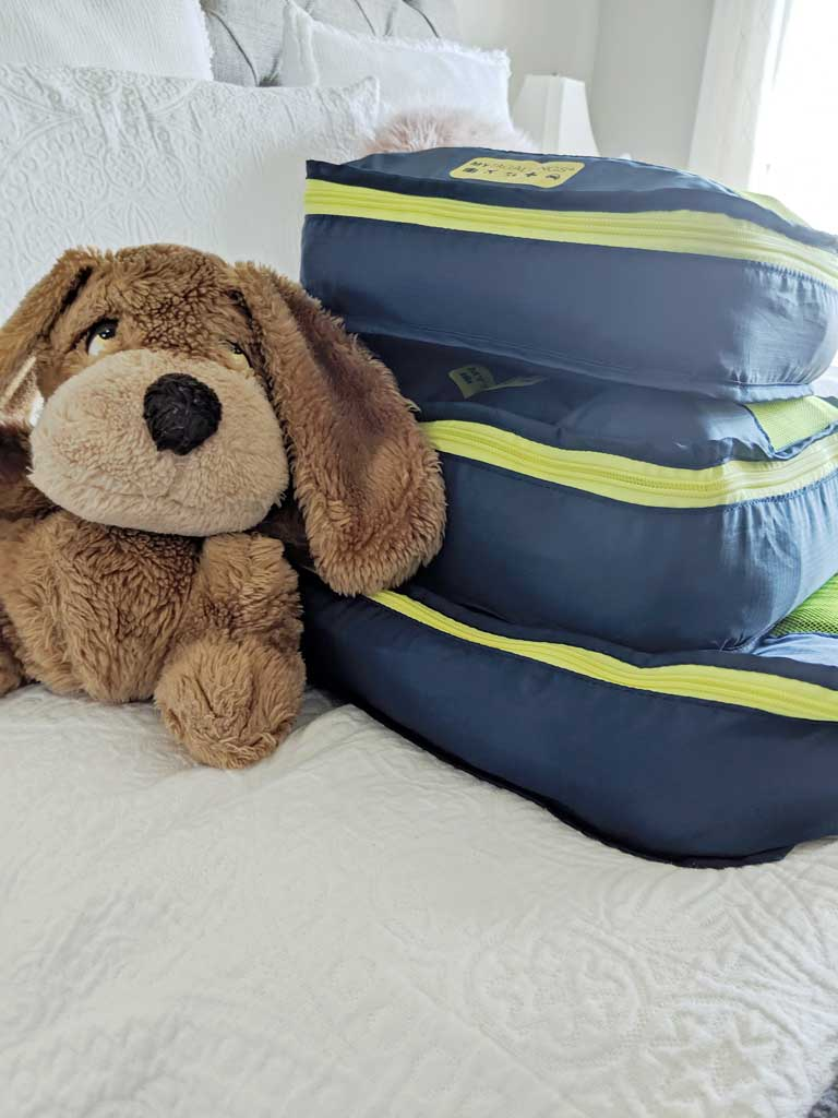 baby travel essentials in packing cubes next to a stuffed animal