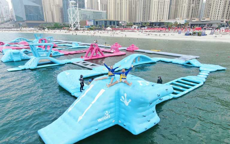 Kids at AquaFun Dubai, the world's largest inflatable water park. A perfect way to cool off in Dubai for kids.