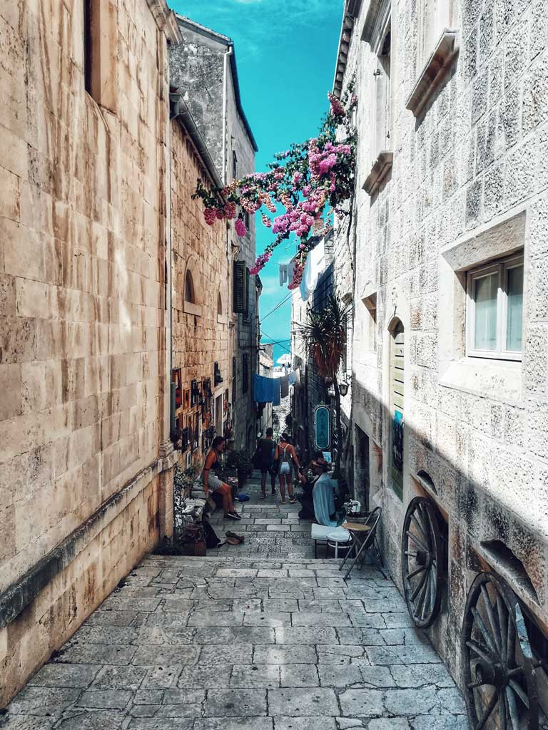 people wandering down a narrow street in Old Town Korcula, one of the best things to do in Korcula, Croatia.