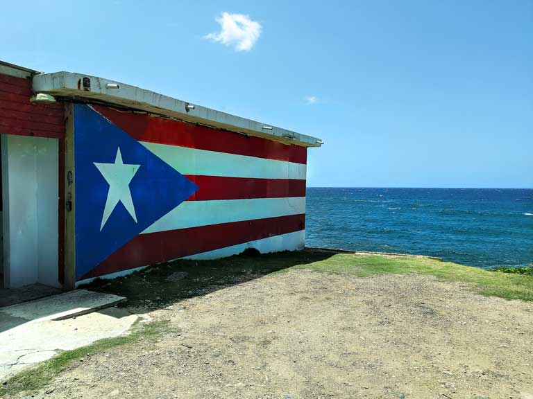 Puerto Rico flag painted on side of building with ocean in the background, found during road trip Puerto Rico