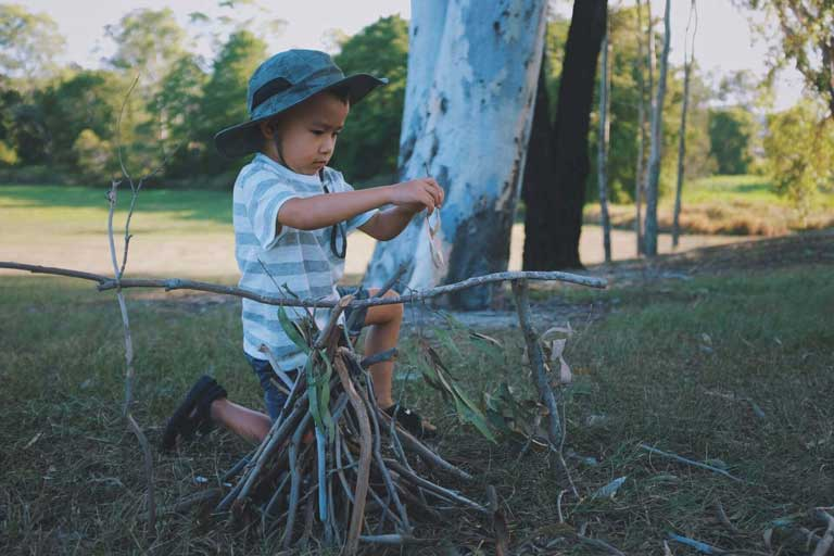 little boy helping to build a fire while camping - letting kids help is a family camping tip to make camping with kids more fun for everyone.
