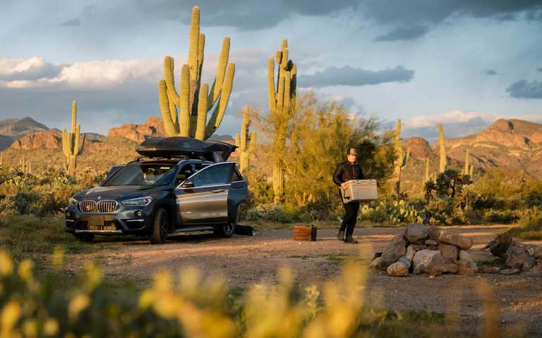man unloading a car on a camping trip - getting organized is one of the best family camping tips to make a camp out easier.
