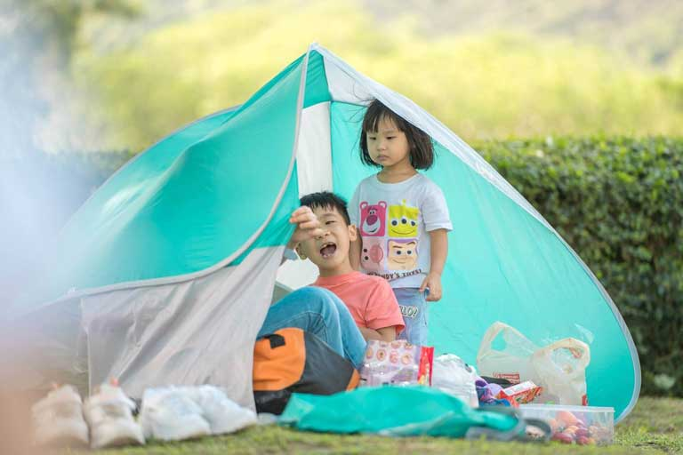 kids playing in a tent in the backyard